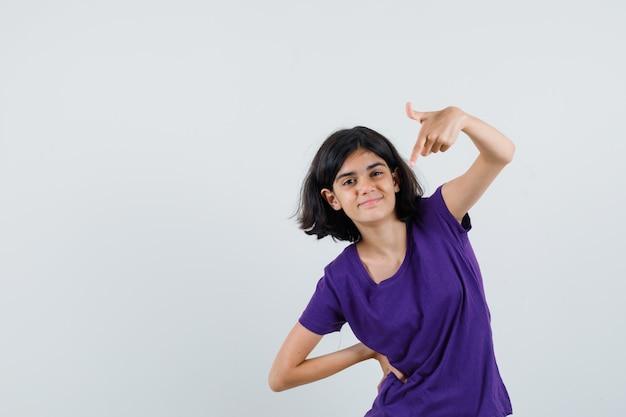 Meisje dat in t-shirt naar beneden wijst en zelfverzekerd kijkt