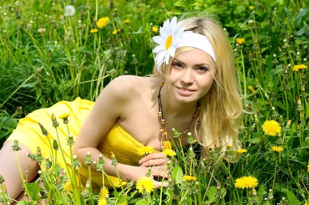 Meisje dat in veld met camomiles ligt.