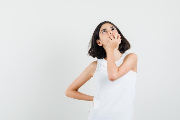 Meisje dat in witte blouse hand op kin houdt en dromerig, vooraanzicht kijkt.