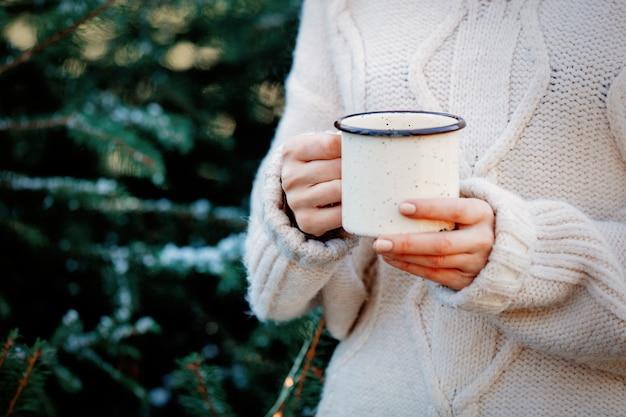 Meisje dat in witte sweater een kop met koffie houdt dichtbij spar