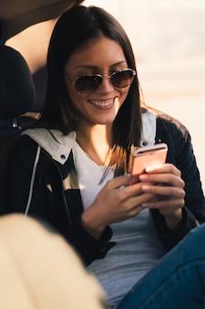 Meisje dat in zonnebril en een bericht in de auto glimlacht leest