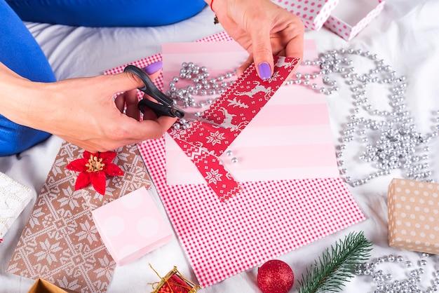 Meisje dat kerstkaarten en decoratie voor familie en kerstboom maakt. vieringen, verjaardagsfeest, cadeautjes,