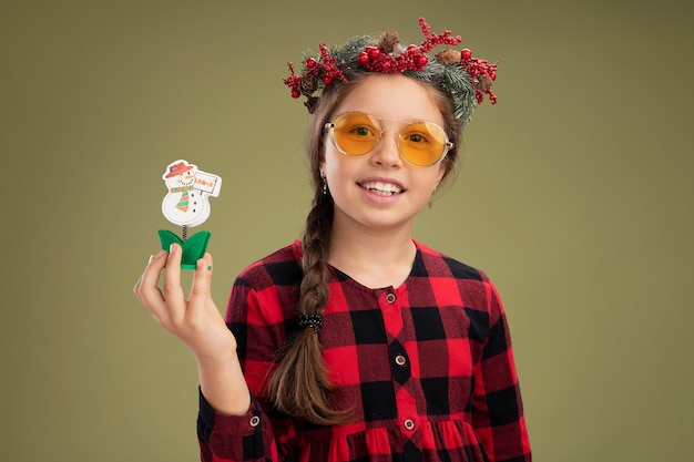 Meisje dat kerstmiskroon draagt in gecontroleerde kleding die kerstmisstuk speelgoed houdt die camera gelukkig en positief glimlachend status over groene achtergrond bekijken