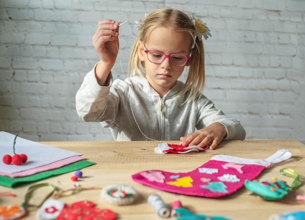 Meisje dat kerstviltdecoratie maakt, kind nieuwjaarsdecor van vilt maakt
