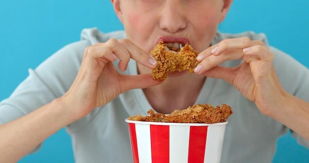 Meisje dat kippenvleugels eet