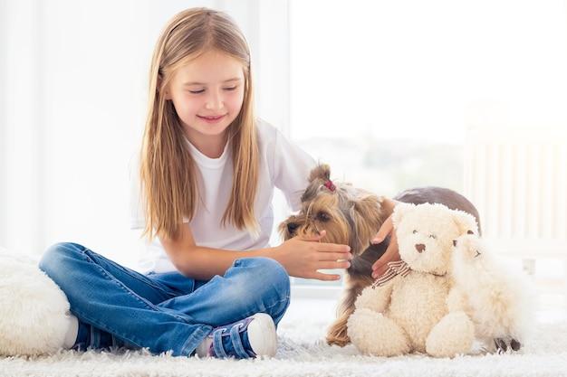 Meisje dat kleine hond in lichte ruimte vangt