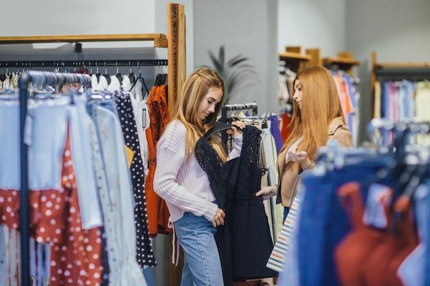 Meisje dat kleren in de winkel kiest
