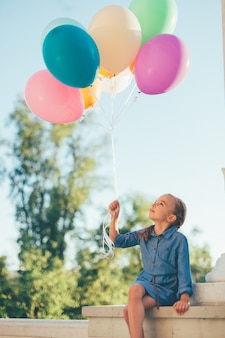 Meisje dat kleurrijke ballons houdt kijkend aan hen