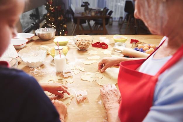 Meisje dat koekje met oma maakt