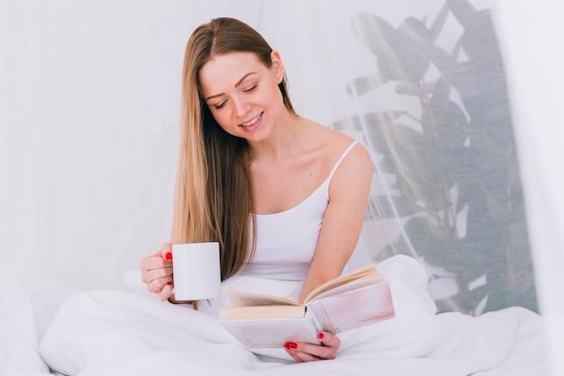 Meisje dat koffie met een boek op het bed heeft