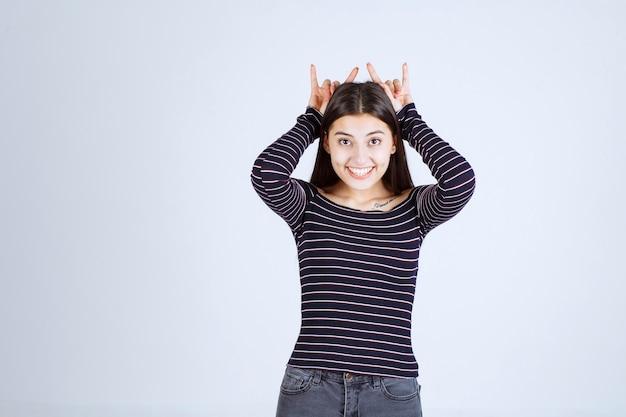 Meisje dat konijn of wolfsoorteken toont.