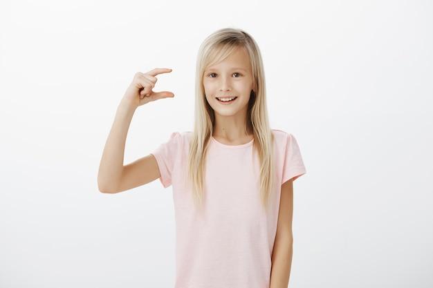 Meisje dat laat zien hoeveel moeite het kost om gelukkig te zijn. binnen schot van helder vriendelijk blond vrouwelijk kind in roze t-shirt, iets kleins of kleins shapink en breed glimlachend, opgewonden en vreugdevol