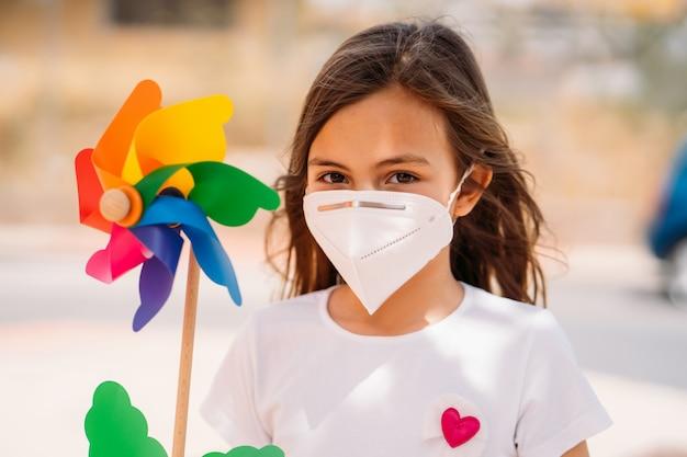 Meisje dat masker draagt en een kleurrijke windmolen houdt