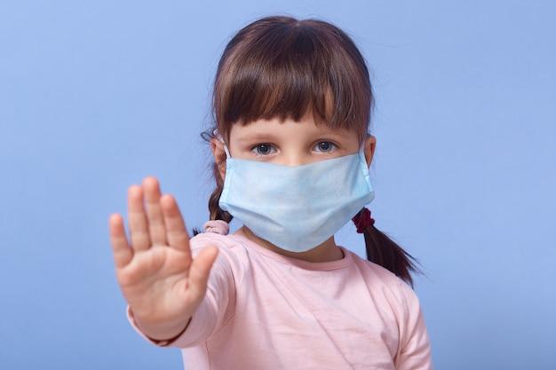 Meisje dat medisch gezichtsmasker draagt en eindeteken met haar palm maakt