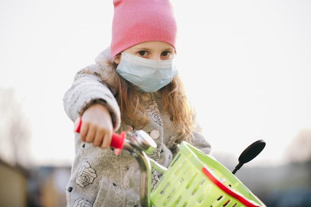 Meisje dat medisch masker draagt tijdens de eponemie van het coronavirus. ziek meisje dat bescherming draagt tijdens pandemie. vrij jong kaukasisch meisje die medisch masker overnemen openlucht