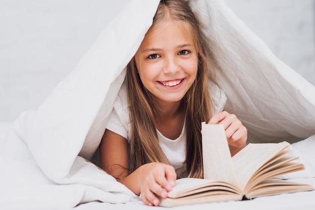 Meisje dat met boek de camera bekijkt