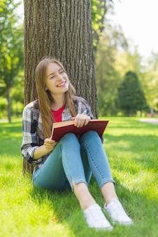 Meisje dat met boek weg kijkt