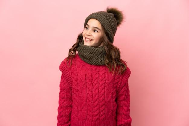 Meisje dat met de winterhoed op roze muur wordt geïsoleerd die een idee denkt terwijl het opzoeken