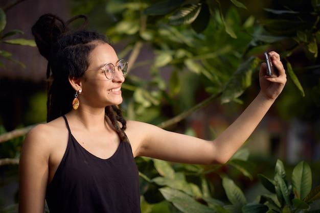 Meisje dat met dreadlocks een zelfportret met haar celtelefoon neemt.