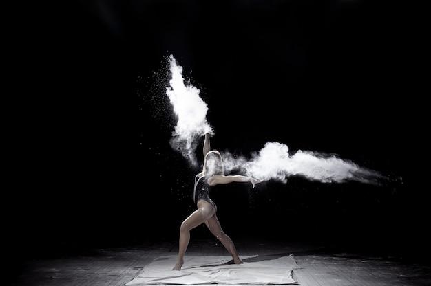 Meisje dat met een bloem op de zwarte achtergrond op sceene danst