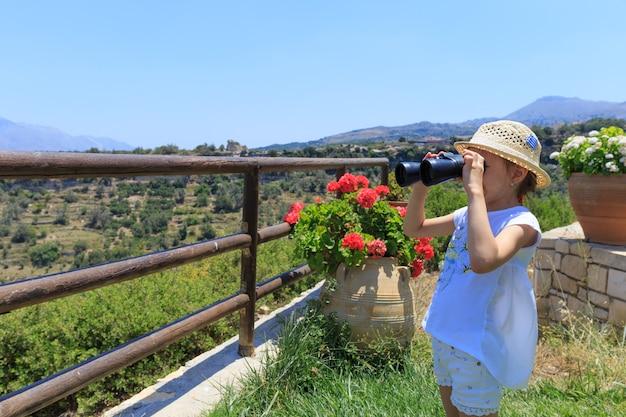 Meisje dat met een verrekijker de verte onderzoekt. bergen op de achtergrond.