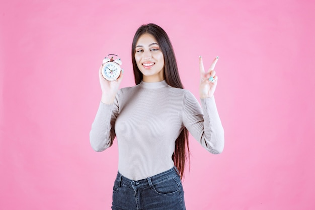 Meisje dat met een wekker vredesteken maakt