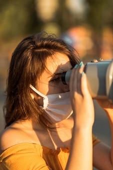 Meisje dat met gezichtsmasker door een verrekijker kijkt naar de zonsondergang.