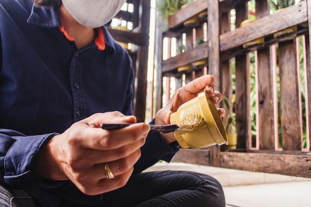 Meisje dat met gezichtsmasker een aangepaste bloempot schildert met een penseel