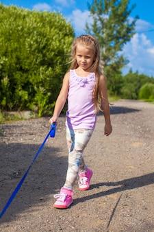 Meisje dat met haar hond aan de leiband loopt