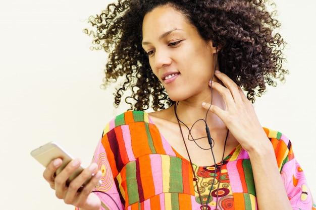 Meisje dat met haar mobiele telefoon naar muziek luistert en een hoofdtelefoon gebruikt