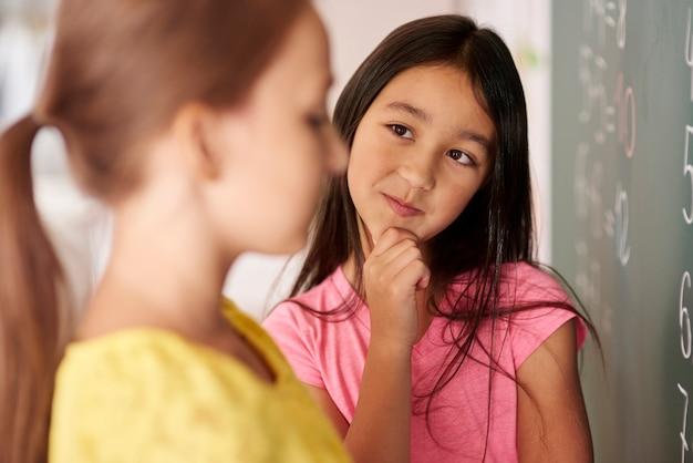 Meisje dat met hand op kin klasgenoot bekijkt