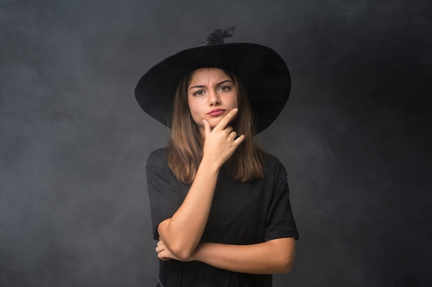 Meisje dat met heksenkostuum voor halloween-partijen over geïsoleerde donkere muur een idee denkt