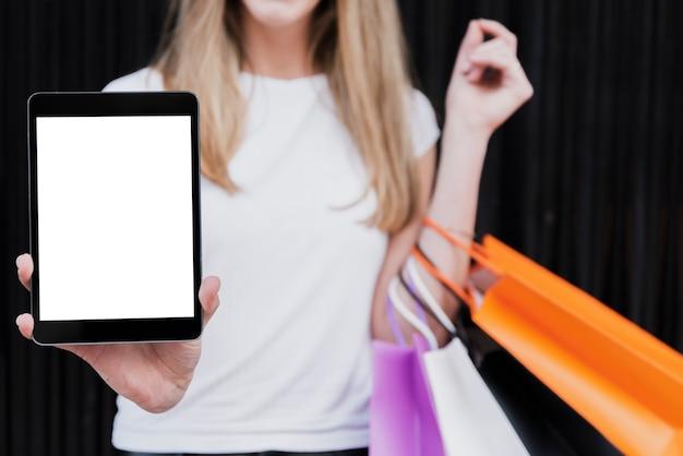 Meisje dat met het winkelen zakken tabletmodel houdt