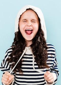 Meisje dat met hoodie grappige gezichten maakt