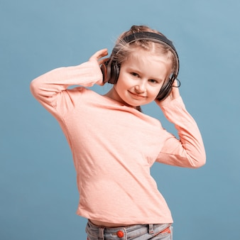 Meisje dat met hoofdtelefoons aan muziek luistert