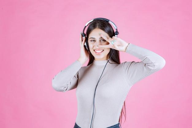 Meisje dat met hoofdtelefoons de muziek luistert en vredesteken toont