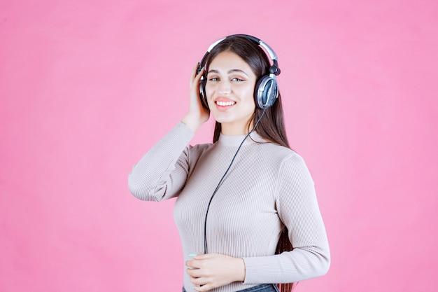 Meisje dat met hoofdtelefoons de muziek luistert en zich gelukkig voelt