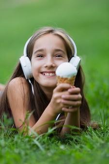 Meisje dat met hoofdtelefoons roomijs eet