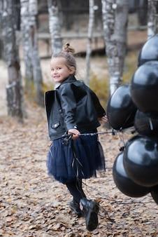 Meisje dat met in hand ballons loopt. kid plezier in zomer park. outdoor activiteiten