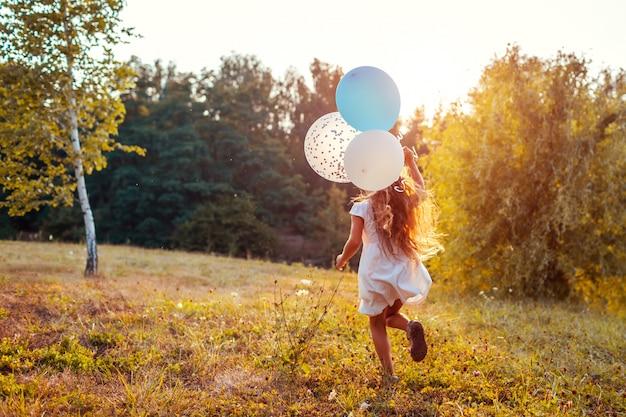Meisje dat met in hand baloons loopt. kid plezier in zomer park. outdoor activiteiten
