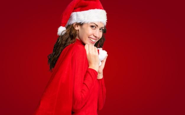 Meisje dat met kerstmishoed een hoogtepunt van de kerstmiszak van giften over geïsoleerde rode muur houdt