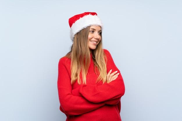 Meisje dat met kerstmishoed over geïsoleerde blauwe muur aan de kant kijkt