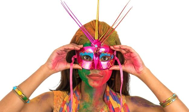 Meisje dat met kleurrijk gezicht carnaval-masker houdt en holi viert.