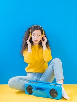 Meisje dat met krullend haar aan muziek luistert