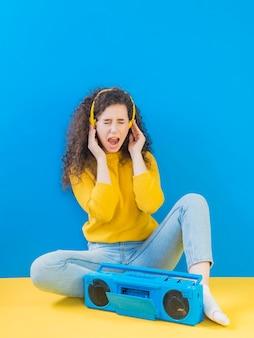 Meisje dat met krullend haar aan retro muziek luistert