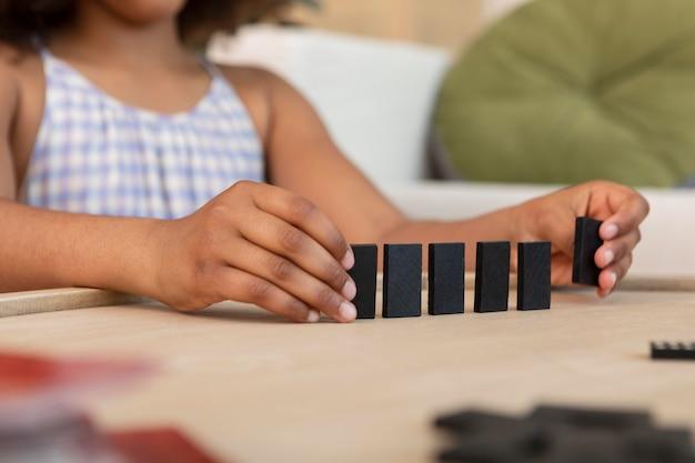Meisje dat met krullend haar met dominostukken speelt