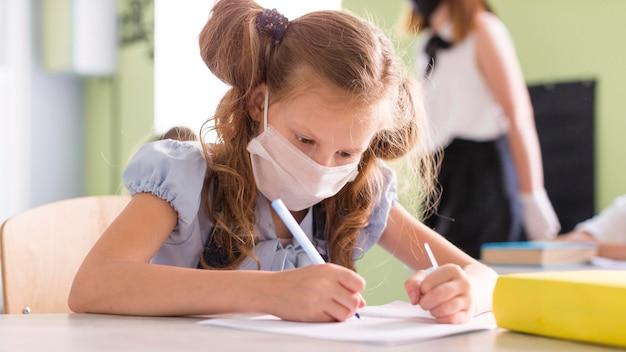 Meisje dat met medisch masker een nieuwe les schrijft
