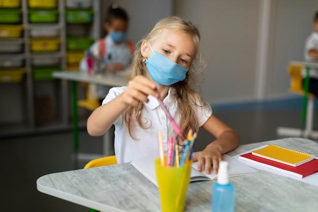 Meisje dat met medisch masker een potlood neemt