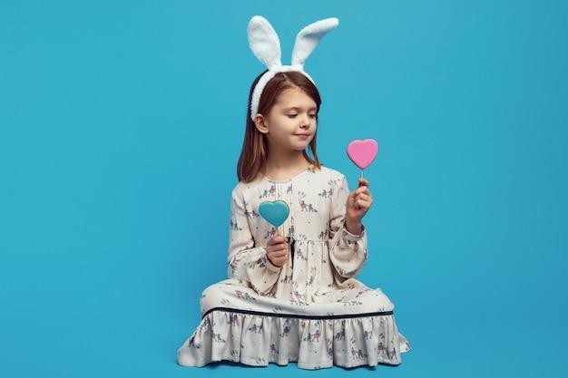Meisje dat met paashaasoren twee koekjes in hartvorm op stokken houdt
