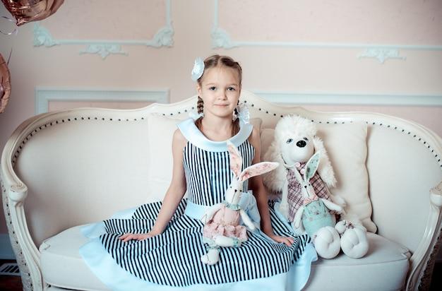 Meisje dat met speelgoed op bank zit